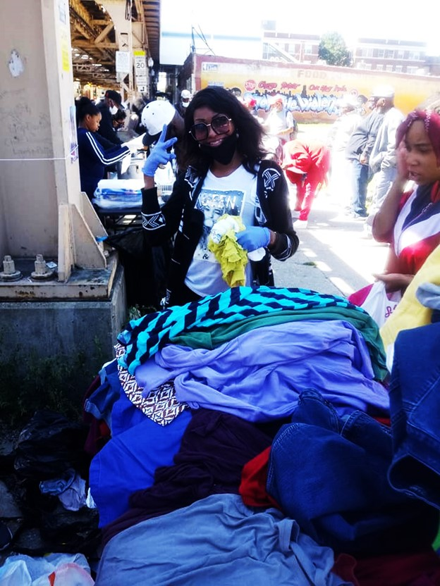 lady smiling, peace hand sign, holding clothing donation itemsitems